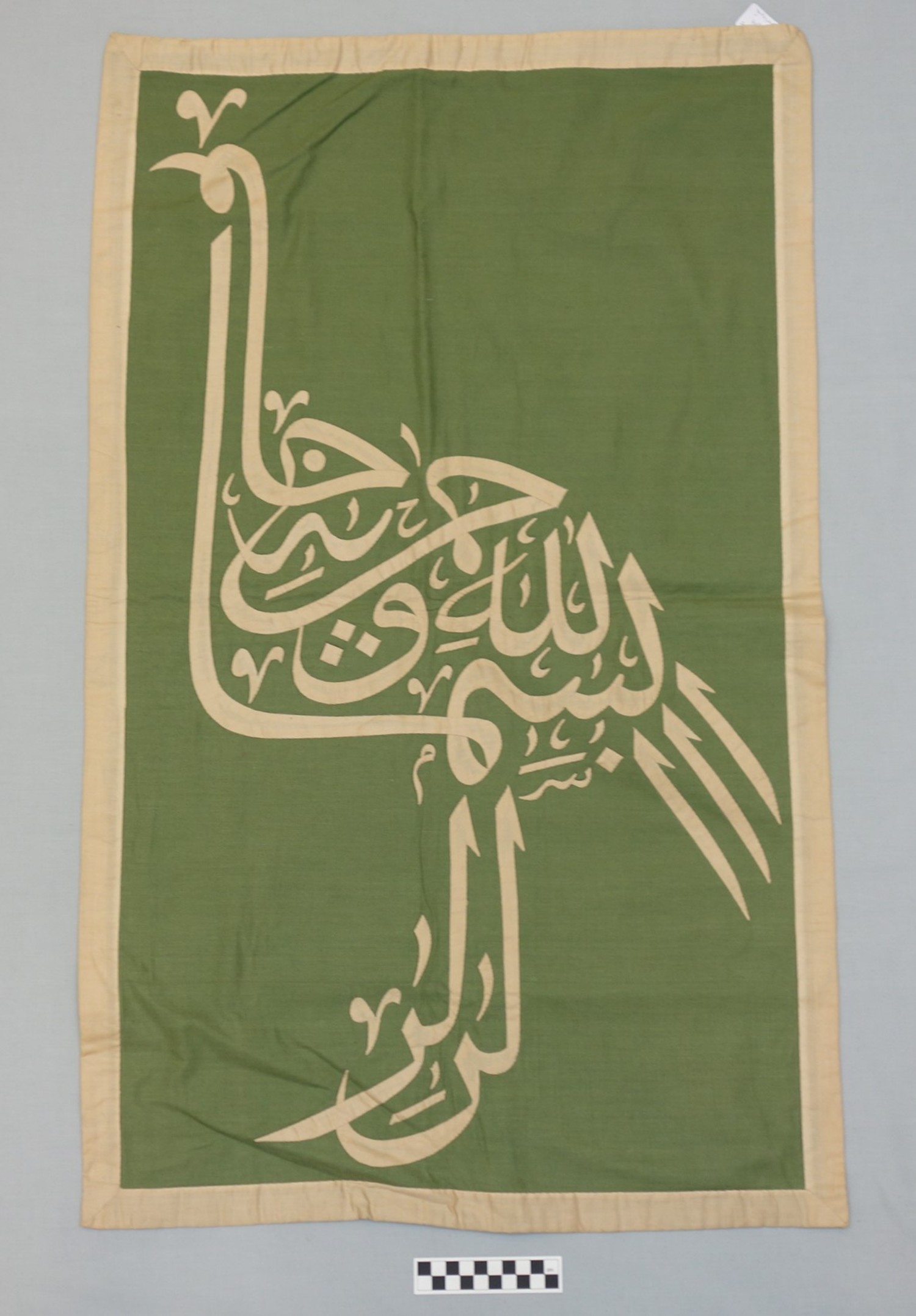 Appliqué panel from the Street of the Tentmakers, Cairo, Egypt (TRC 2014.0818), showing a text written in the shape of a bird. For more information, click on the illustration.