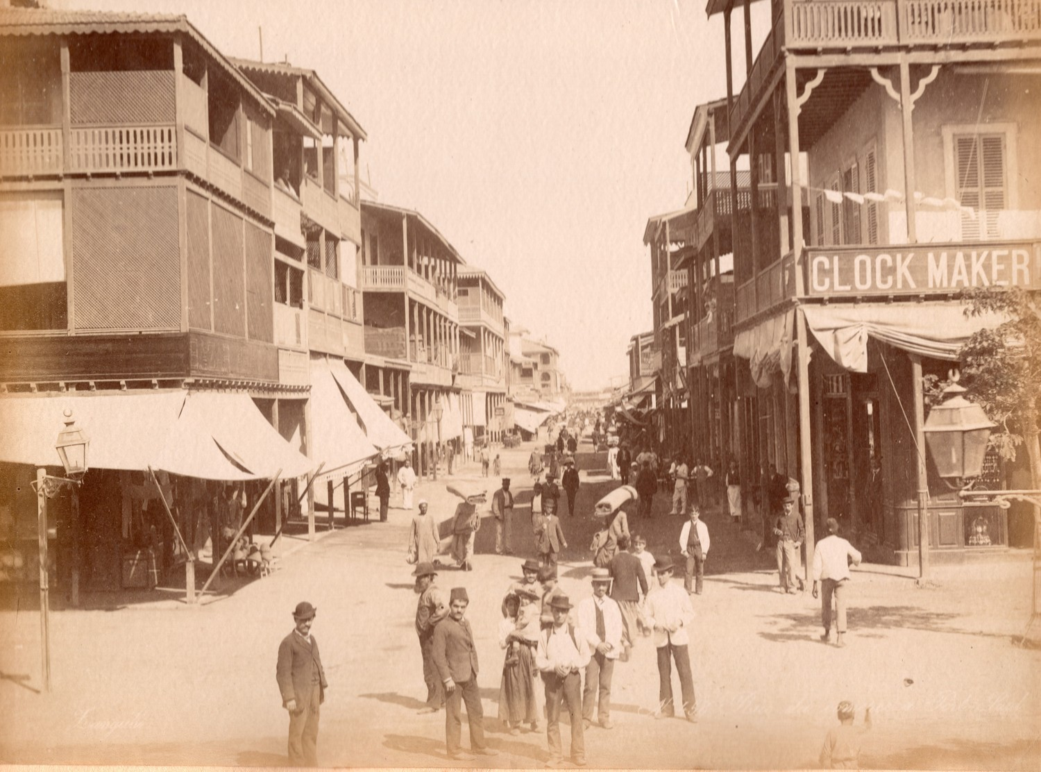 Photograph of a street in Port Said (Rue de Commerce), Egypt, late 19th century, showing people wih Arab, Turkish and Western styles of dress.