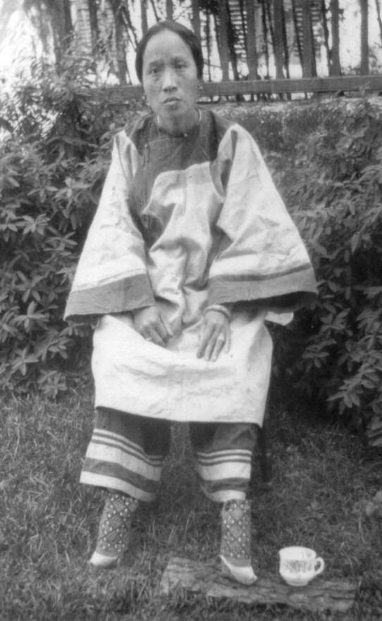 Chinese woman with small bound feet and leggings that are worn under her main, baggy trousers (c. 1905; courtesy of the Library of Congress, LC-USZ62-80735).