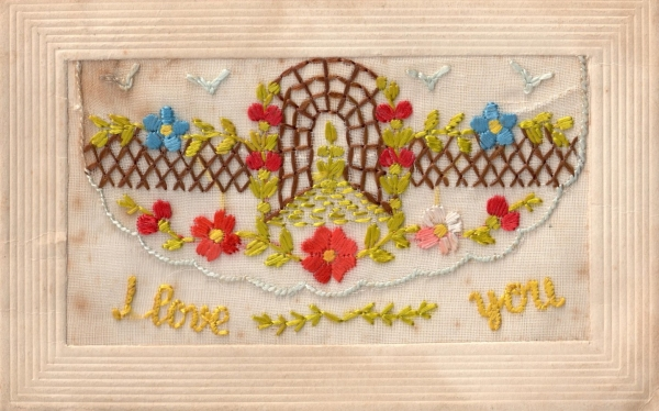 "Early 20th century silk embroidered postcard with the text ""I love you""."