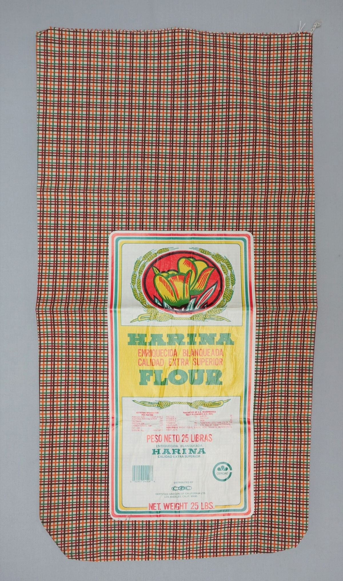 Large sack made from cotton with a printed checked design in brown, dark red, green and orange. With barcode. USA, 1960's.