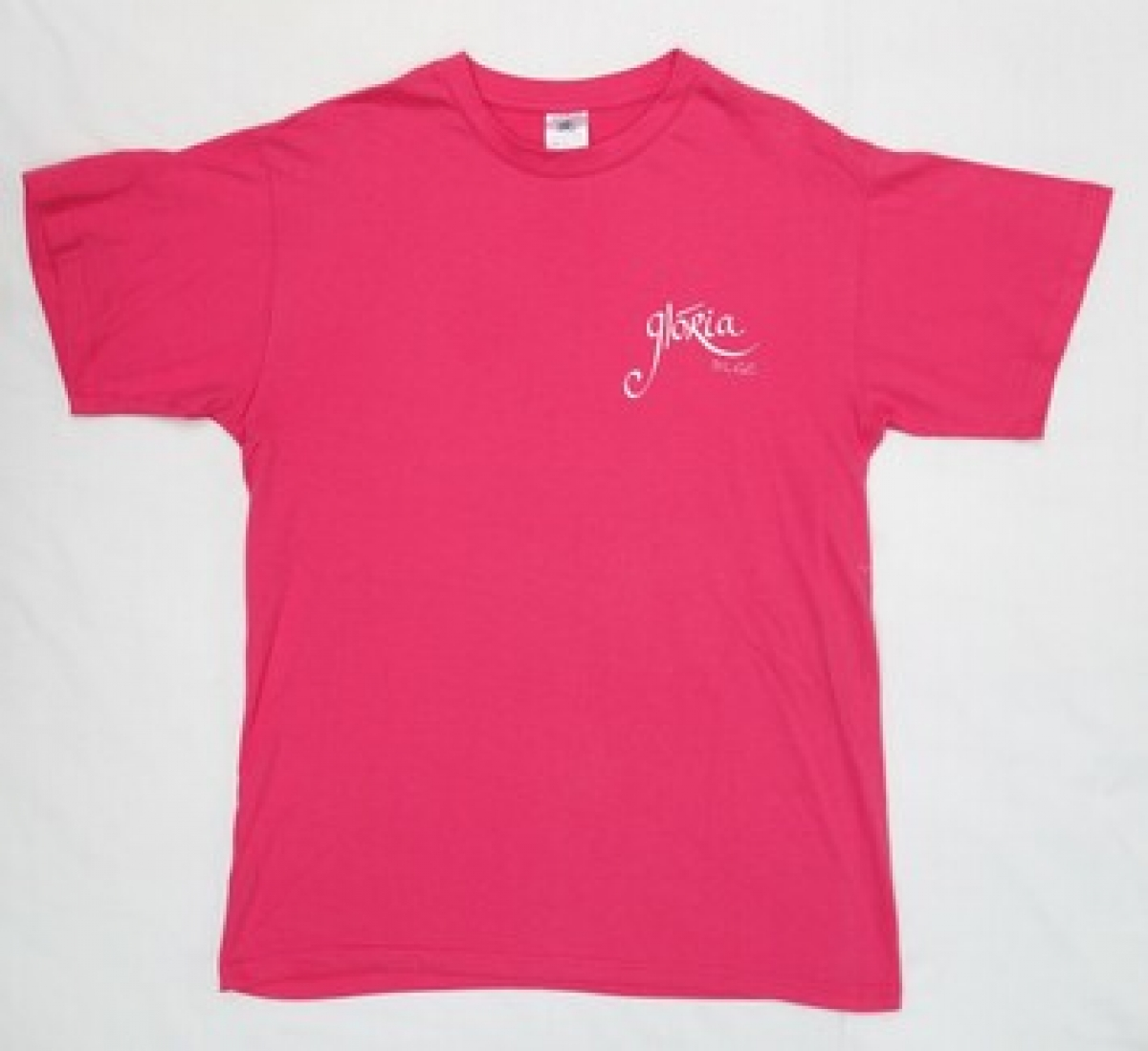 A pink t-shirt with the name GLÓRIA DLGC on the front and a large stylised shamrock with VARIOUS VOICES DUBLIN on the back. Ireland, early 21st century.