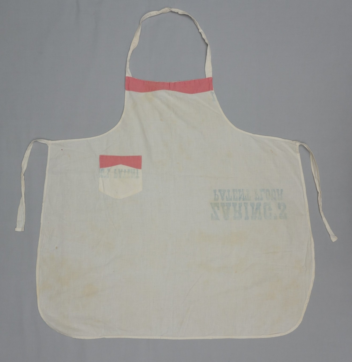 Bibbed apron with a small pocket made from bleached flour sacks. Parts of the bib and the pocket have been decorated with applied cotton cloth in pink.