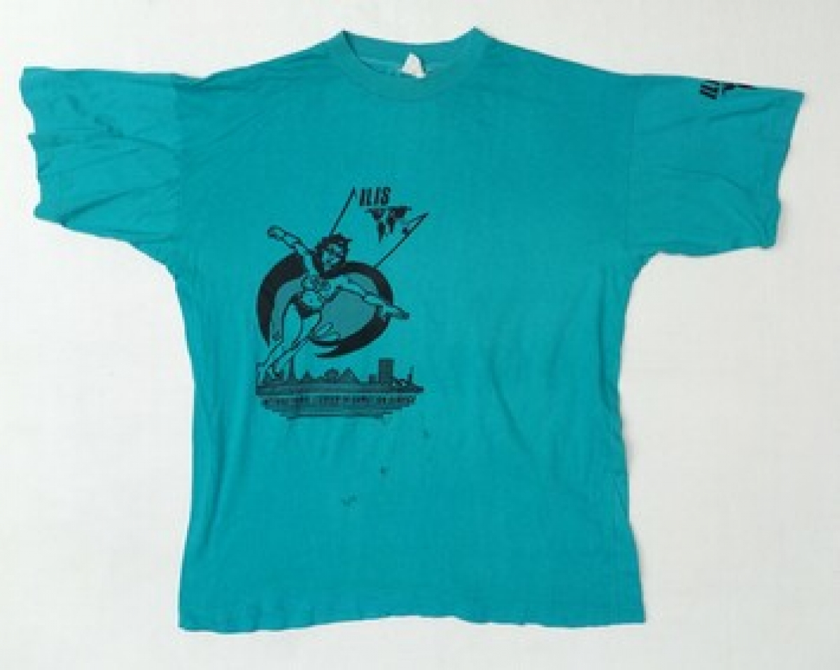 Turquoise T-shirt with a black image of a super heroine and the initials ILIS (International Lesbian Information Service).