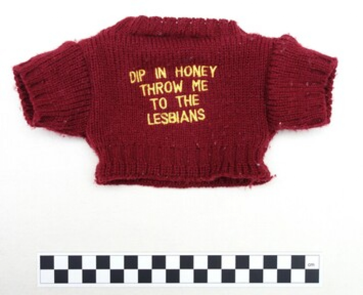 "Mini jumper in dark red with the text: ""DIP IN HONEY THROW ME TO THE LESBIANS"". Early 1990s, UK."