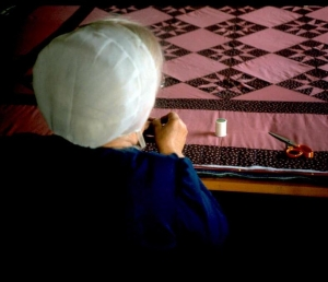 Amish woman working a quilt.