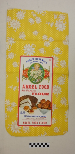 Flour sack made from bright yellow cloth with printed flowers, to be used for clothing or other domestic textiles. USA, 1960s.