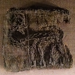 This piece of embroidery depicts a stag turning its head. It is carried out in the couching technique. A grave find from Björkö (Birka), Adelsö, Uppland, Sweden.