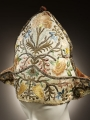 A mid-18th century undress cap from Italy. It is decorated with stylised flowers, as well as metal threads and spangles.