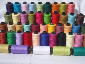 Assortment of industrially produced cotton threads.