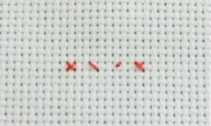 Piece of Aida material with a simple cross stitch indicated in red.