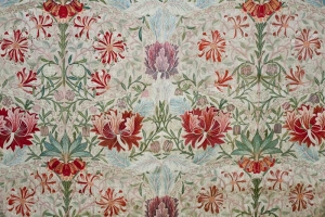 Detail of a silk and linen hanging (267 x 150 cm) decorated with a honeysuckle motif, designed by William Morris in 1876, and embroidered by Jane and their daughter Jenny Morris, c. 1880's. This piece was displayed at the 1914 Louvre exhibition of British and Irish decorative needlework.