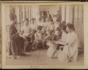 Photograph of embroidery workshop in Rasht, Iran, with man being bastinadoed. Dated c. 1880.