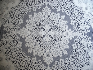 Detail of an oval table cloth made of quaker lace.
