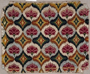 An example of a seat cover decorated with geometric and stylised flowers in Florentine work. It is worked on a linen canvas ground using silk threads (early 18th century; British)
