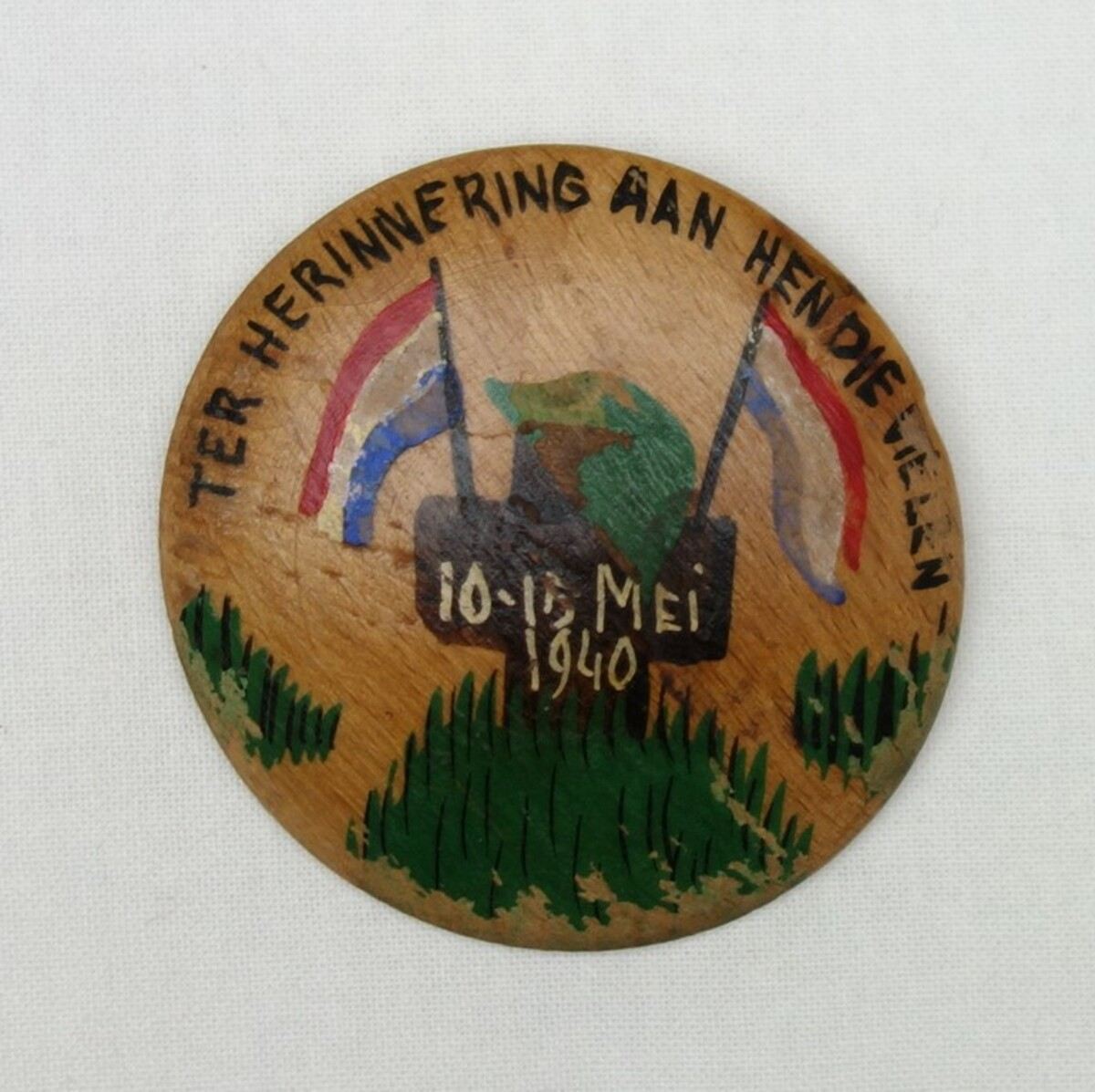 A painted brooch made of wood, with a personal memento of the German attack on The Netherlands in May 1940. 'Ter herinnering aan hen die vielen. 10-15 mei 1940' (TRC 2019.2292).