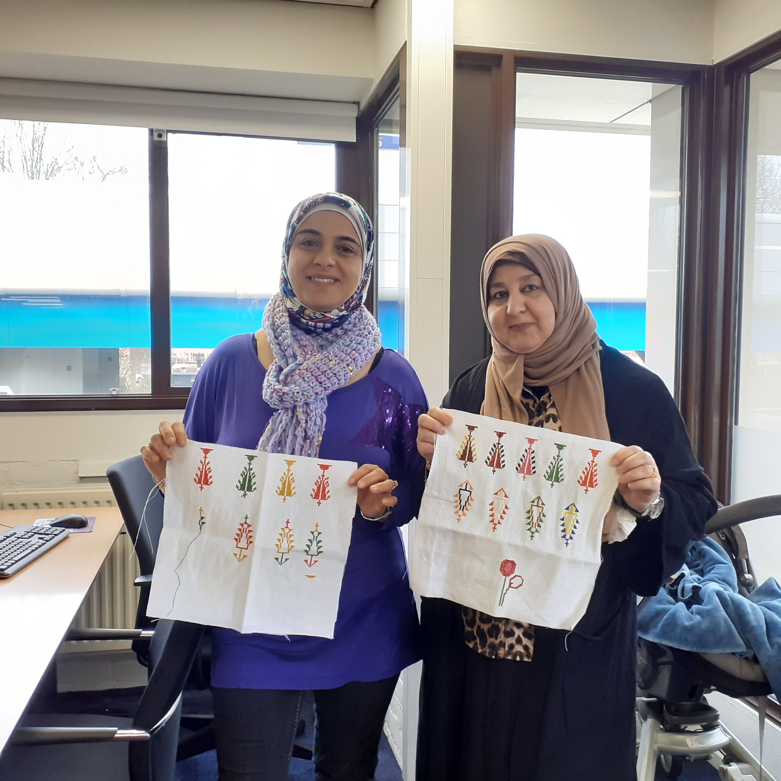 Two Middle Eastern women in Capelle a/d IJssel, proudly showing their embroidery.