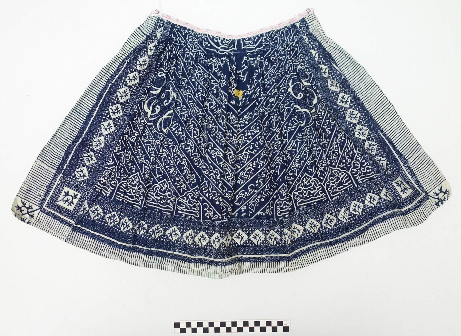 Boy's apron (locally called a boezel) from the Dutch island of Marken, made from a cotton, indigo resist-dyed Indonesian batik textile with Arabic (style) script, early 20th century (TRC 2009.0048).