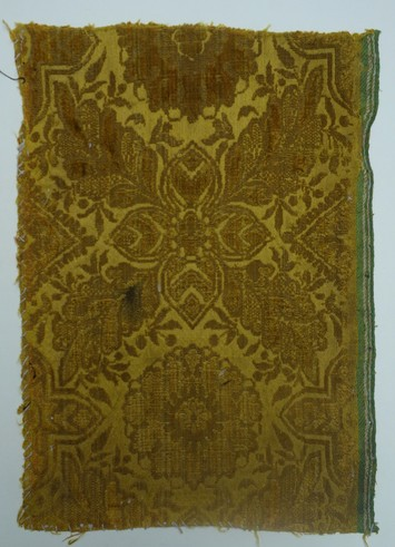Early 17th century voided velvet sample, with cut and uncut pile (ciselé), satin ground and a green and white selvedge (TRC 2011.0376).
