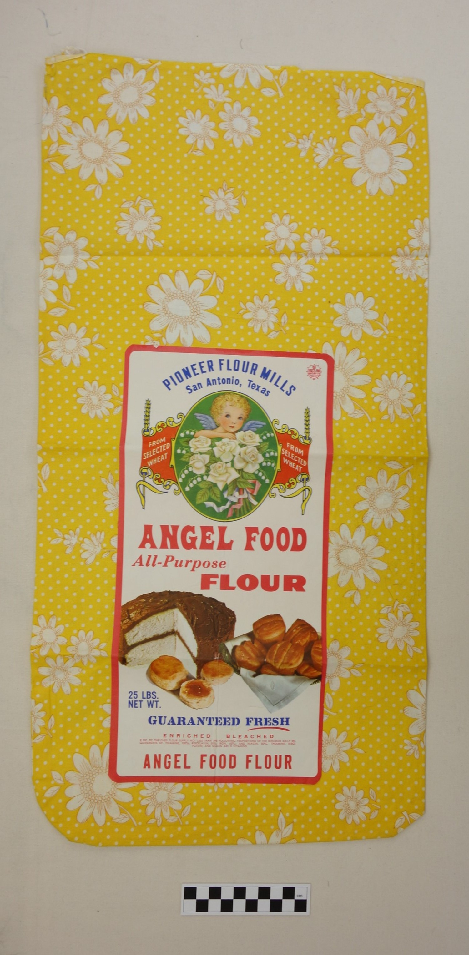 Flour sack made from bright yellow cloth with printed flowers, to be used for clothing or other domestic textiles. USA, 1960s (TRC 2017.2403).
