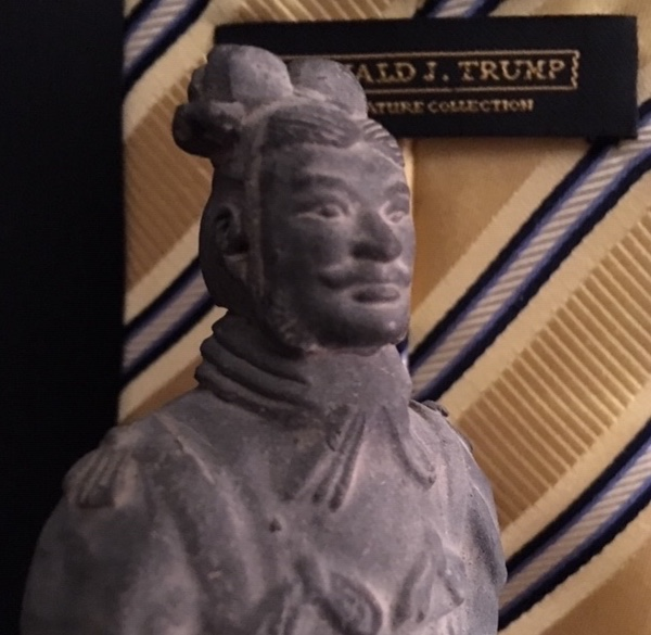 Statue from the tomb of the Chinese emperor Qin Shi Huang (died c. 210 BC) of a terracotta soldier with neckband. In the background a tie label from President Donald Trump's fashion line of ties (coincidentally made in China).